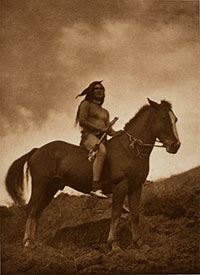 sepia-toned historical photo of a Native American man on a horse