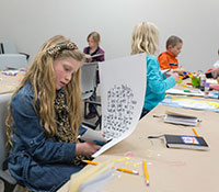 young girl cutting paper at a table with other children and art supplies