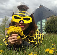 person lying in the grass wearing a bee-like mask and holding flowers