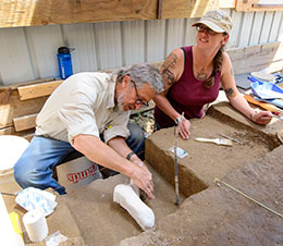 man and woman sitting and cleaning items from archaeological dig