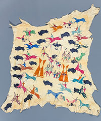 animal hide with small pictures of buffalo, people and horses and teepees all over it