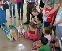 children clustered around a shining spot on the floor