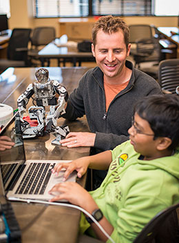 man with small robot talking to boy at computer keyboard