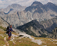 man with backpack on a mountainside with peaks in the background