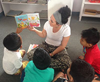 woman reading to several small children