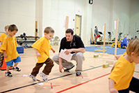 man working with small children in gym
