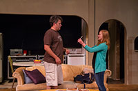 woman showing something to a man in front of a sofa on a stage set