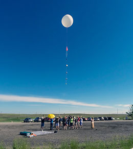people watching a weather balloon ascend