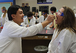 young man in lab coat using swab in the mouth of a young woman in lab coat