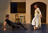 on a stage, a woman approaches a man on the floor