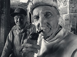 black and white photo of someone smoking a pipe with another person in the background