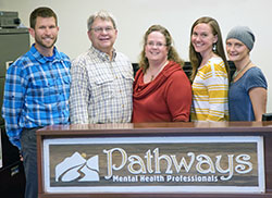 five people standing behind a counter with a sign that says Pathways