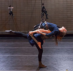 two dancers wearing lift harnesses