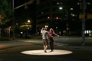 two people dancing outside in the dark