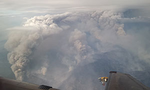 wing of aircraft above billows of wildfire smoke