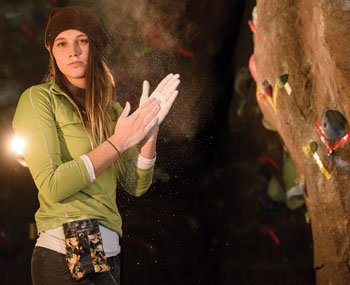 woman rubbing chalk on her hands preparing to rock climb