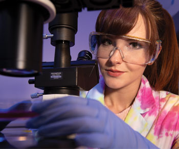 woman in safety glasses using a microscope