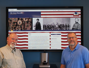 two men standing in front of a video display