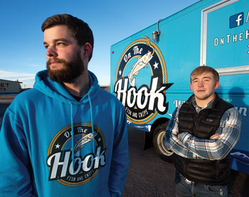 two men in front of a food truck