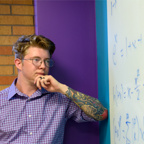 McNair Scholar Clay Carper stands in front of a white board with equations on it