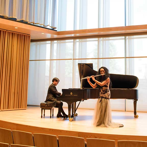 Picture of students performing on the piano and flute