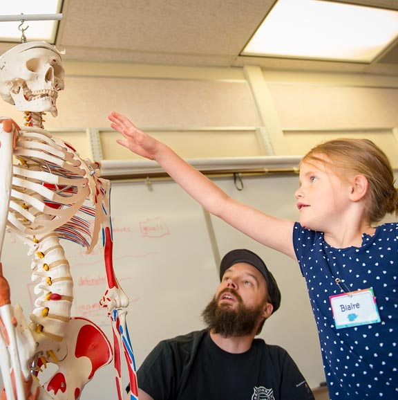Student teacher working with child and skeleton