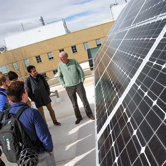Picture of students in front of a large solar panel