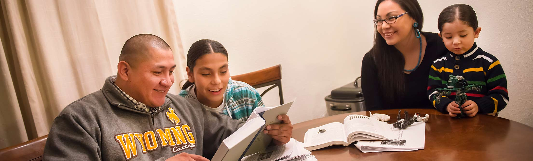 UW Student reading and smiling while reading a book at home.