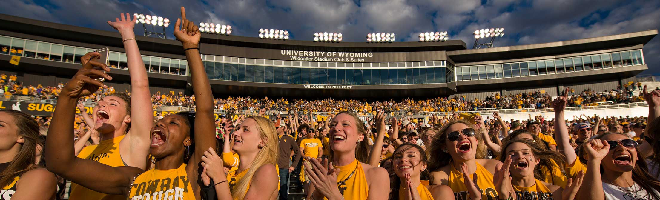 UW students in gold cheering in the football stadium during a game