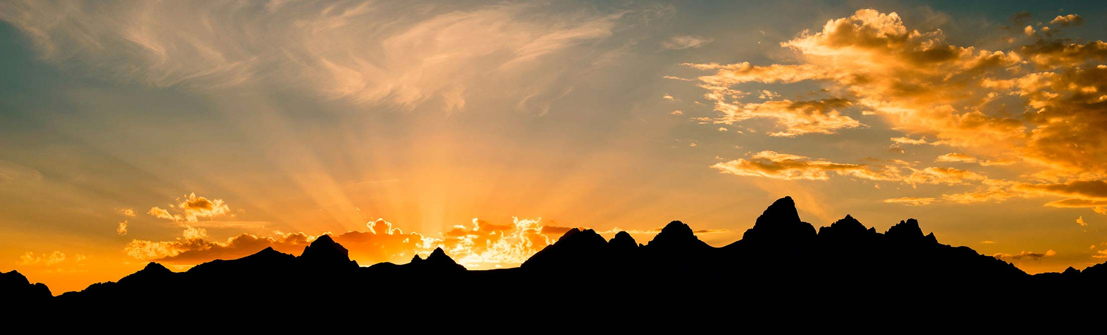 sun setting behind the tetons; mountains in silhouette