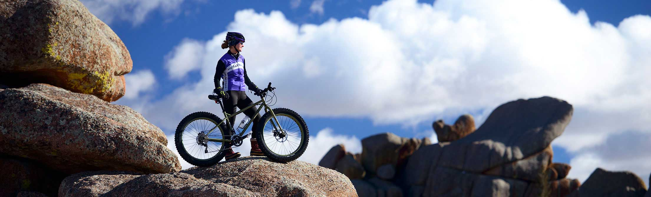 Biker on top of large rock formation on mountain