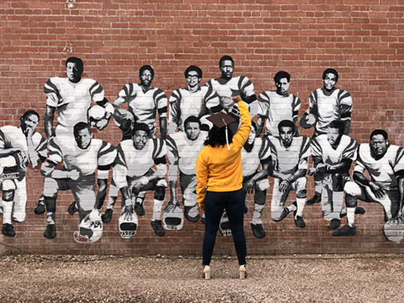 Graduate Olivia Cole facing black 14 mural with right fist raised
