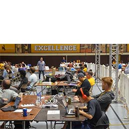Group of coders sit at a table in the War Memorial Fieldhouse