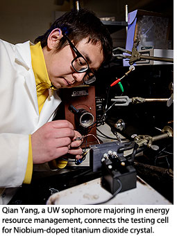 Qian Yang, a UW sophomore majoring in energy resource management, connects the testing cell for Niobium-doped titanium dioxide crystal.