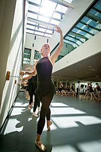dancers practicing in a sunny studio, with one hand on the barre