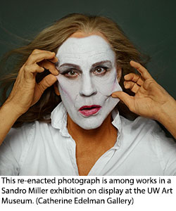 photo of woman with white face paint pulling at skin on face to distort it