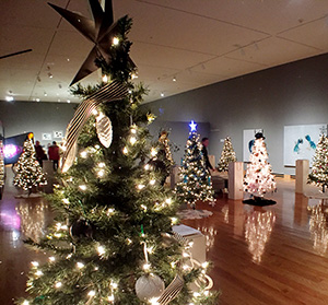 multiple Christmas trees in a large room with shiny wood floors