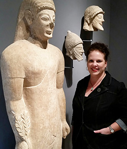 photo of a woman standing beside an Egyptian statue