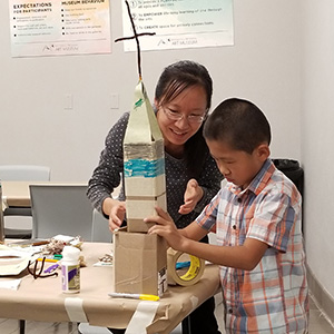 woman and boy making something out of cardboard boxes