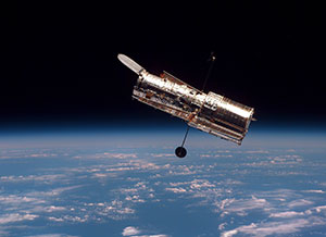 The Hubble Space Telescope moves slowly away from the space shuttle Discovery.