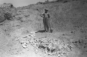 old black and white photo of a man with a pile of bones