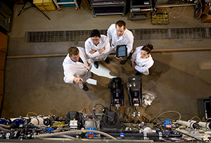 overhead view of four people in white coats looking at equipment