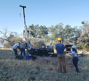 people in field with geoprobe